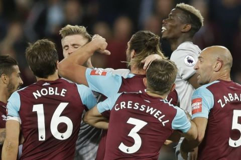 West Ham United players and Manchester United players engage in a bit of pushing during the English Premier League soccer match between West Ham United and Manchester United at the London Stadium in London, Thursday, May 10, 2018. (AP Photo/Alastair Grant)