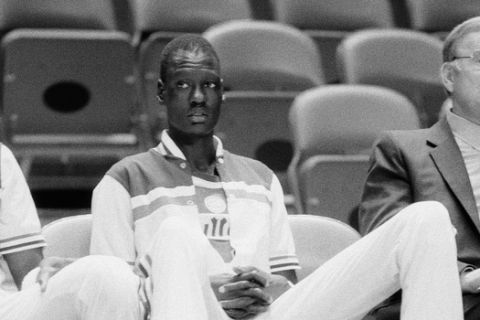 Manute Bol of the Washington Bullets is shown on the sidelines during the game between the Bullets and the San Antonio Spurs, Oct. 17, 1985.  (AP Photo/G. Paul Burnett)