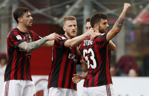 AC Milan's Patrick Cutrone, right, celebrates with his teammates after scoring his side's second goal during the Serie A soccer match between AC Milan and Hellas Verona at the San Siro stadium in Milan, Italy, Saturday, May 5, 2018. (AP Photo/Antonio Calanni)