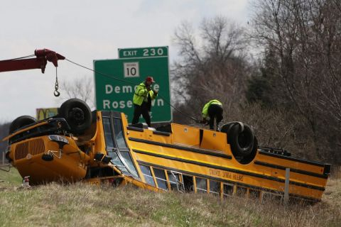 A school bus which was carrying the Griffith High School basketball team is towed away after the bus overturned in Demotte, Ind., Saturday, March 19, 2016. A northwest Indiana high school basketball coach was airlifted to a hospital Saturday after a driver who spilled her drink sideswiped the bus carrying 27 players and staff, causing it to overturn on Interstate 65. (Jonathan Miano/The Times via AP) MANDATORY CREDIT