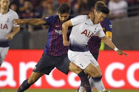 Barcelona midfielder Andre Gomes, front left, battles for the ball with Tottenham forward Son Heung-Min during the first half of an International Champions Cup tournament soccer match Saturday, July 28, 2018, in Pasadena, Calif. (AP Photo/Mark J. Terrill)