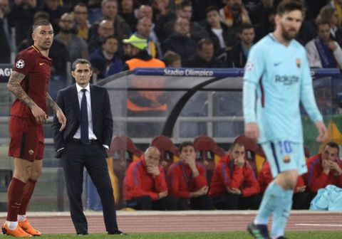 Barcelona coach Ernesto Valverde, second left, watches his players as Roma's Juan Jesus, left, and Barcelona's Lionel Messi, right, wait for the game to resume during the Champions League quarterfinal second leg soccer match between between Roma and FC Barcelona, at Rome's Olympic Stadium, Tuesday, April 10, 2018. (AP Photo/Gregorio Borgia)
