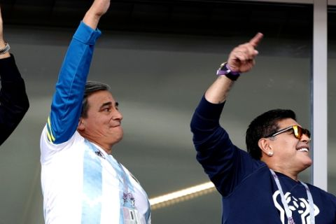 Former soccer star Diego Maradona, right, cheers Argentina's team as he attends the group D match between Argentina and Iceland at the 2018 soccer World Cup in the Spartak Stadium in Moscow, Russia, Saturday, June 16, 2018. (AP Photo/Ricardo Mazalan)