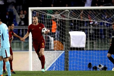 Roma's Edin Dzeko, third from left, is congratulated by teammate Roma's Kevin Strootman, second left, after he scored his side's first goal passing Barcelona goalkeeper Marc-Andre ter Stegen, right, during the Champions League quarterfinal second leg soccer match between between Roma and FC Barcelona, at Rome's Olympic Stadium, Tuesday, April 10, 2018. (AP Photo/Gregorio Borgia)