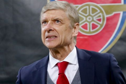 FILE - In this Thursday, March 8, 2018 file photo Arsenal's manager Arsene Wenger waits for the kick-off of the Europa League, round of 16 first-leg soccer match between AC Milan and Arsenal, at the Milan San Siro stadium, Italy. Arsenal manager Arsene Wenger says he will leave the English club at the end of the season after more than 21 years in charge. (AP Photo/Antonio Calanni, File)