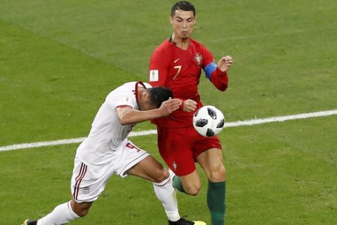 Portugal's Cristiano Ronaldo, right, challenges for the ball with Iran's Omid Ebrahimi during the group B match between Iran and Portugal at the 2018 soccer World Cup at the Mordovia Arena in Saransk, Russia, Monday, June 25, 2018. (AP Photo/Darko Bandic)