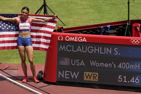 Η Σίντνεϊ ΜακΛάφλιν ποζάρει δίπλα στον πίνακα που αναγράφει το παγκόσμιο ρεκόρ της