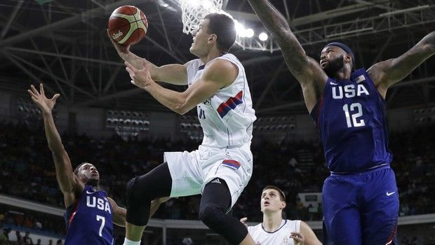 Serbia's Nemanja Nedovic (11) drives to the basket as United States' DeMarcus Cousins (12) and United States' Kyle Lowry (7) defend during the men's gold medal basketball game at the 2016 Summer Olympics in Rio de Janeiro, Brazil, Sunday, Aug. 21, 2016. (AP Photo/Eric Gay)