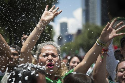 A fan waves her hand in the air as someone else sprays foam during the celebration of Mexico's 2018 World Cup win over Germany, at the Angel of Independence in Mexico City, Sunday, June 17, 2018. Mexico won it's first match against Germany 1-0. (AP Photo/Anthony Vazquez)