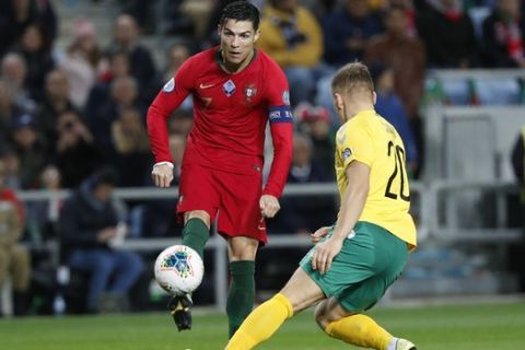 Portugal's Cristiano Ronaldo, left, fights for the ball with Lithuania's Domantas Simkus during the Euro 2020 group B qualifying soccer match between Portugal and Lithuania at the Algarve stadium outside Faro, Portugal, Thursday, Nov. 14, 2019. (AP Photo/Armando Franca)