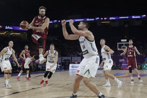 Latvia's Zanis Peiners, with a ball, tries to score as Slovenia's Gasper Vidmar, right, blocks him during their Eurobasket European Basketball Championship quarterfinal match in Istanbul, Tuesday, Sept. 12. 2017. (AP Photo/Thanassis Stavrakis)