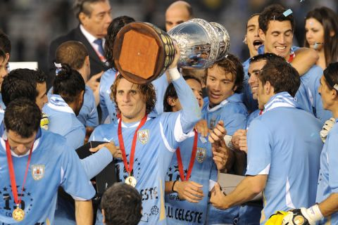 Uruguayan forward Diego Forlan (C) holds the trophy and celebrates with teammates at the end of the 2011 Copa America football tournament final against Paraguay held at the Monumental stadium in Buenos Aires, on July 24, 2011. Uruguay won 3-0 and became champion of the 2011 Copa America.  AFP PHOTO / JUAN MABROMATA (Photo credit should read JUAN MABROMATA/AFP/Getty Images)