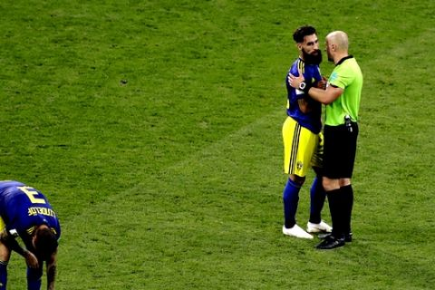Referee Szymon Marcniak of Poland, right, talks with Sweden's Jimmy Durmaz, middle, at the end the group F match between Germany and Sweden at the 2018 soccer World Cup in the Fisht Stadium in Sochi, Russia, Saturday, June 23, 2018. (AP Photo/Sergei Grits)