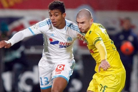 Marseille's French midfielder Mario Lemina, left, challenges for the ball with Nantes' French midfielder Vincent Bessat, during their League One soccer match, at the Velodrome Stadium, in Marseille, southern France, Friday, Dec. 6, 2013. (AP Photo/Claude Paris)