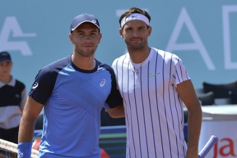 In this photo taken Saturday, June 20, 2020, Bulgaria's Grigor Dimitrov, right, poses for cameras with Croatia's Borna Coric during their semifinal match at a tournament in Zadar, Croatia. Dimitrov says he has tested positive for COVID-19 and his announcement led to the cancellation of an exhibition event in Croatia where Novak Djokovic was scheduled to play on Sunday. (AP Photo/Zvonko Kucelin)