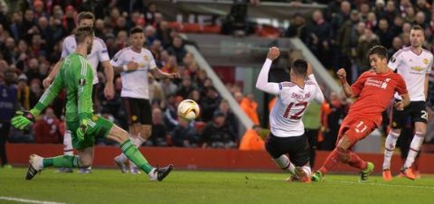 """""""Liverpool's Brazilian midfielder Roberto Firmino (2R) shoots past Manchester United's Spanish goalkeeper David de Gea (L) to score his team's second goal during the UEFA Europa League round of 16, first leg football match between Liverpool and Manchester United at Anfield in Liverpool, northwest England on March 10, 2016. / AFP / PAUL ELLIS        (Photo credit should read PAUL ELLIS/AFP/Getty Images)"""""""