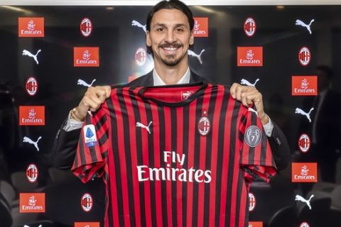 Zlatan Ibrahimovic holds an AC Milan jersey as he poses photos at the team's headquarters, in Milan, Italy, Thursday, Jan. 2, 2020.  The 38-year-old striker has returned to the club he left nearly eight years ago and needs to make an immediate impact on a team in 11th place and still reeling from a 5-0 defeat to Atalanta. (Claudio Furlan/LaPresse via AP)