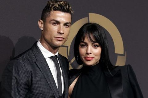 FILe - In this March 19, 2018 file photo, Real Madrid player Cristiano Ronaldo and his girlfriend Georgina Rodriguez pose for photos as they arrive for the Portuguese soccer federation awards ceremony in Lisbon. (AP Photo/Armando Franca, File)