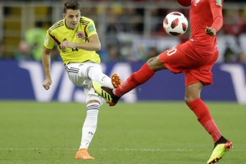 Colombia's Santiago Arias, left, kicks the ball as England's Dele Alli tries to stop him during the round of 16 match between Colombia and England at the 2018 soccer World Cup in the Spartak Stadium, in Moscow, Russia, Tuesday, July 3, 2018. (AP Photo/Matthias Schrader)