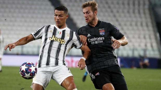 Juventus' Cristiano Ronaldo, left, controls the ball as Lyon's Joachim Andersen defends during the Champions League round of 16 second leg, soccer match between Juventus and Lyon at the Allianz stadium in Turin, Italy, Friday, Aug. 7, 2020. (AP Photo/Antonio Calanni)