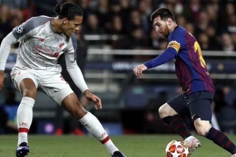 Liverpool's Virgil Van Dijk, left, vies for the ball with Barcelona's Lionel Messi during the Champions League semifinal, first leg, soccer match between FC Barcelona and Liverpool at the Camp Nou stadium in Barcelona Spain, Wednesday, May 1, 2019. (AP Photo/Joan Monfort)