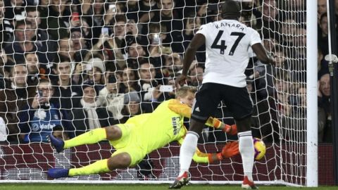Fulham's Aboubakar Kamara has a penalty saved by Huddersfield Town goalkeeper Jonas Lossl, during their English Premier League soccer match at Craven Cottage in London, Saturday Dec. 29, 2018. (Yui Mok/PA via AP)
