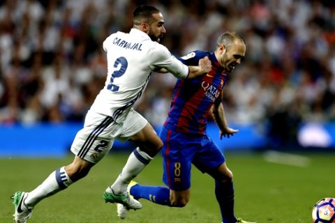 Barcelona's Andres Iniesta, right, challenges for the ball with Real Madrid's Daniel Carvajal during a Spanish La Liga soccer match between Real Madrid and Barcelona, dubbed 'el clasico', at the Santiago Bernabeu stadium in Madrid, Spain, Sunday, April 23, 2017. (AP Photo/Francisco Seco)