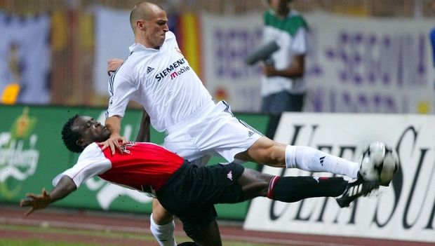 Feyenoord's Chris Gyan, left, fights for the ball with Real Madrid's Esteban Cambiasso Deleau during the UEFA Super Cup final soccer match at the Louis II stadium in Monaco, Friday, Aug. 30, 2002. (AP Photo/Lionel Cironneau)