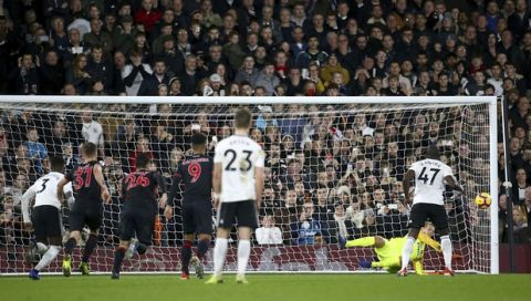 Fulham's Aboubakar Kamara, 47, right, has a penalty saved by Huddersfield Town goalkeeper Jonas Lossl, during their English Premier League soccer match at Craven Cottage in London, Saturday Dec. 29, 2018. (Yui Mok/PA via AP)
