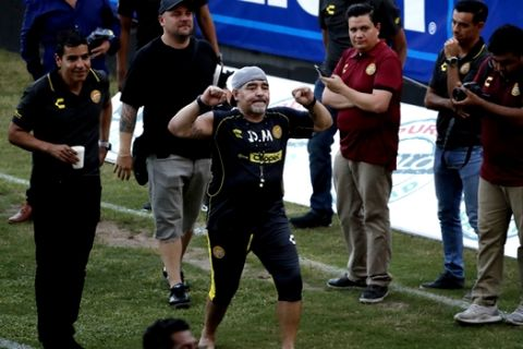 Former soccer great Diego Maradona says goodbye to the fans in stands, after a training session at the Dorados de Sinaloa soccer club stadium, after Maradona was presented as the new manager of the Dorados in Culiacan, Mexico, Monday, Sept. 10, 2018. Maradona, whose public battles with cocaine made him soccer's poster child for the perils of substance abuse, is setting up camp in Mexico's drug cartel heartland as the new coach of a second-tier team. (AP Photo/Marco Ugarte)