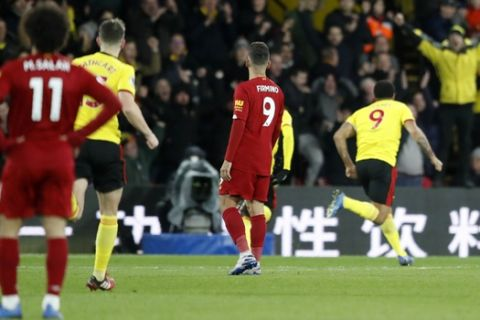 Liverpool's Roberto Firmino, center, and Liverpool's Mohamed Salah, left, react after Watford's Troy Deeney, right, scores his side's third goal during the English Premier League soccer match between Watford and Liverpool at Vicarage Road stadium, in Watford, England, Saturday, Feb. 29, 2020. (AP Photo/Alastair Grant)