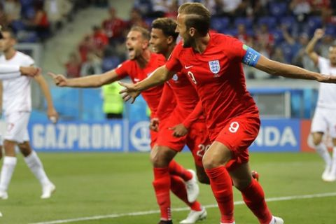 England's Harry Kane, foreground right, celebrates after scoring his side's opening goal against Tunisia during the group G match between Tunisia and England at the 2018 soccer World Cup in the Volgograd Arena in Volgograd, Russia, Monday, June 18, 2018. (AP Photo/Sergei Grits)