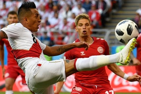 Peru's Christian Cueva, left, vies for the ball with Denmark's LARSEN Jens Strygerd during the group C match between Peru and Denmark at the 2018 soccer World Cup in the Mordovia Arena in Saransk, Russia, Saturday, June 16, 2018. (AP Photo/Martin Meissner)