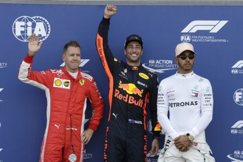 Pole position winner Red Bull driver Daniel Ricciardo of Australia, center, celebrates flanked by third placed Ferrari driver Sebastian Vettel of Germany, left, and second placed Mercedes driver Lewis Hamilton of Britain at the end of the qualifying session for Sunday's Monaco Formula One Grand Prix at the Monaco racetrack, in Monaco, Saturday, May 26, 2018. (AP Photo/Claude Paris)