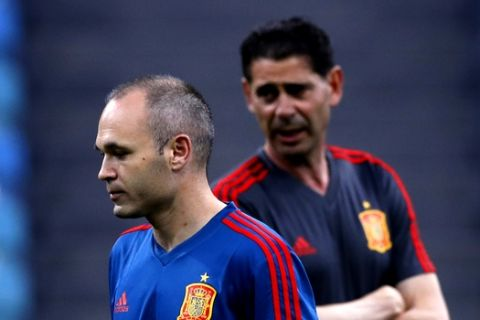 Spain's Andres Iniesta, left, walks next to his coach Fernando Hierro takes part during Spain's official training on the eve of the group B match between Portugal and Spain at the 2018 soccer World Cup in the Fisht Stadium in Sochi, Russia, Thursday, June 14, 2018. (AP Photo/Manu Fernandez)