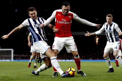 Arsenal's Lucas Perez, centre, vies for the ball with West Brom's Gareth McAuley during the English Premier League soccer match between Arsenal and West Bromwich Albion at Emirates stadium in London, Monday, Dec. 26, 2016. (AP Photo/Kirsty Wigglesworth)