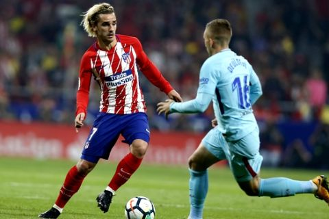Atletico Madrid's Antoine Griezmann, left, tussles for the ball with Barcelona's Gerard Deulofeu during a Spanish La Liga soccer match between Atletico Madrid and Barcelona at the Metropolitano stadium in Madrid, Saturday, Oct. 14, 2017. The match ended in a 1-1 draw. (AP Photo/Francisco Seco)