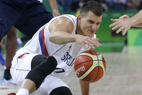 Serbia's Nemanja Nedovic (11) picks up a loose ball in front of France's Thomas Heurtel, right, during a basketball game at the 2016 Summer Olympics in Rio de Janeiro, Brazil, Wednesday, Aug. 10, 2016. (AP Photo/Charlie Neibergall)