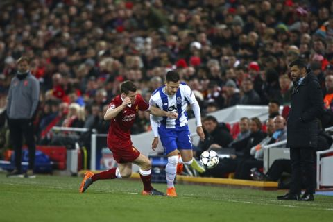 Porto coach Sergio Conceicao , right, and Liverpool coach Jurgen Klopp, left, watch Liverpool's James Milner, enter left, fight for the ball with Porto's Diogo Dalot during the Champions League round of 16, second leg, soccer match between Liverpool and FC Porto at Anfield Stadium, Liverpool, England, Tuesday March 6, 2018. (AP Photo/Dave Thompson)