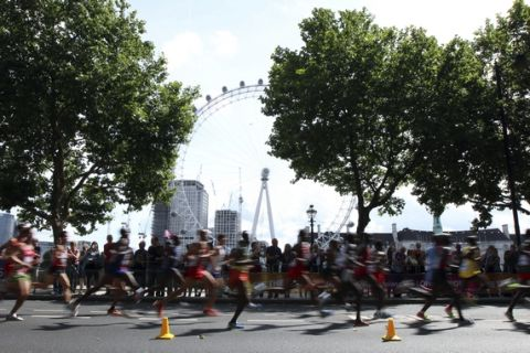 Competitors run past the London Eye as they compete in the Men's Marathon during the World Athletics Championships in London Sunday, Aug. 6, 2017. (AP Photo/Leonore Schick)