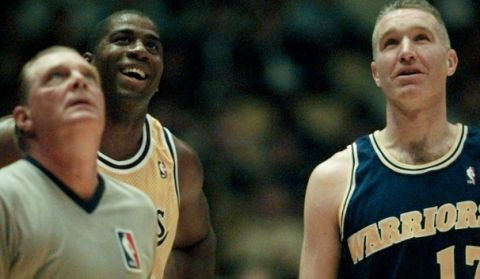 """Los Angeles Lakers Earvin """"Magic"""" Johnson, center, smiles with Golden State Warriors Chris Mullin during their game Tuesday, Jan. 30, 1996, at the Forum in Inglewood, Calif. At left is NBA referee Ed Middleton. Johnson made his NBA comeback Tuesday, after four years off the court. (AP Photo/Damian Dovarganes)"""
