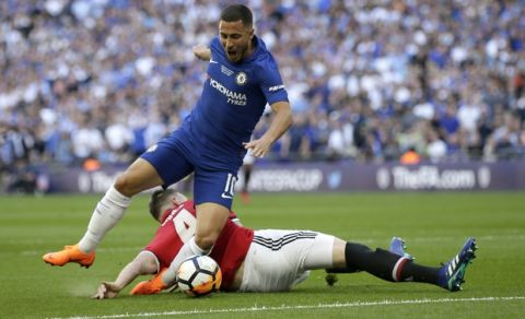 Manchester United's Phil Jones, on the ground, fouls Chelsea's Eden Hazard in the box to give away a penalty shot during the English FA Cup final soccer match between Chelsea and Manchester United at Wembley stadium in London, Saturday, May 19, 2018. (AP Photo/Tim Ireland)