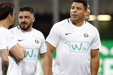 Soccer legend Ronaldo, right, is flanked by Gennaro Gattuso as they enter the pitch prior to Andrea Pirlo farewell exhibition match, at the Milan San Siro Stadium, Italy, Monday, May 21, 2018. (AP Photo/Antonio Calanni)