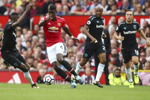Manchester United's Paul Pogba, 2nd left, takes on the West Ham United defence during the English Premier League soccer match between Manchester United and West Ham United at Old Trafford in Manchester, England, Sunday, Aug. 13, 2017. (AP Photo/Dave Thompson)