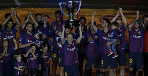 FC Barcelona's Andres Iniesta holds the Spanish La Liga trophy with his teammates after the Spanish La Liga soccer match between FC Barcelona and Real Sociedad at the Camp Nou stadium in Barcelona, Spain, Sunday, May 20, 2018. (AP Photo/Manu Fernandez)
